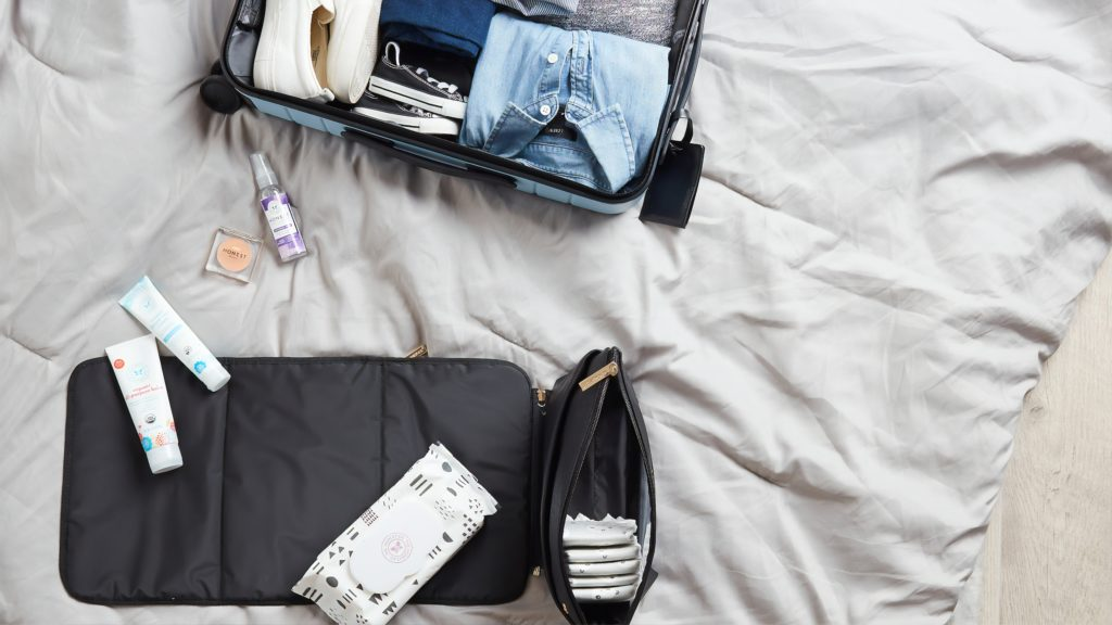 open suitcase with toiletries and clothes being packed