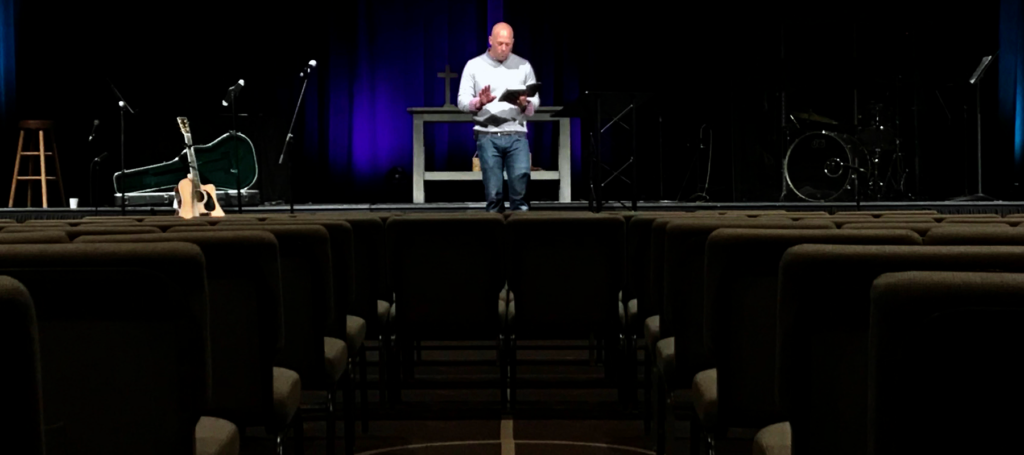 Preacher holding Bible standing at front of empty sanctuary