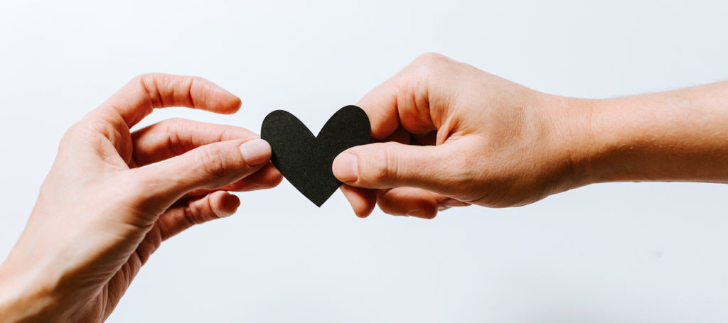 Two hands holding one small black heart between them