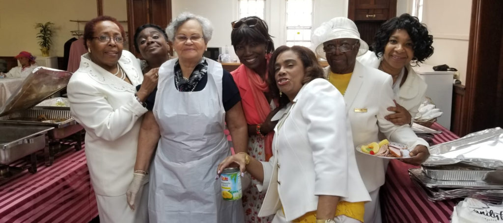 Six women working in a soup kitchen pose for the camera