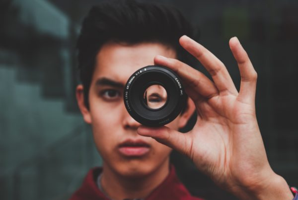 man looks through camera lens