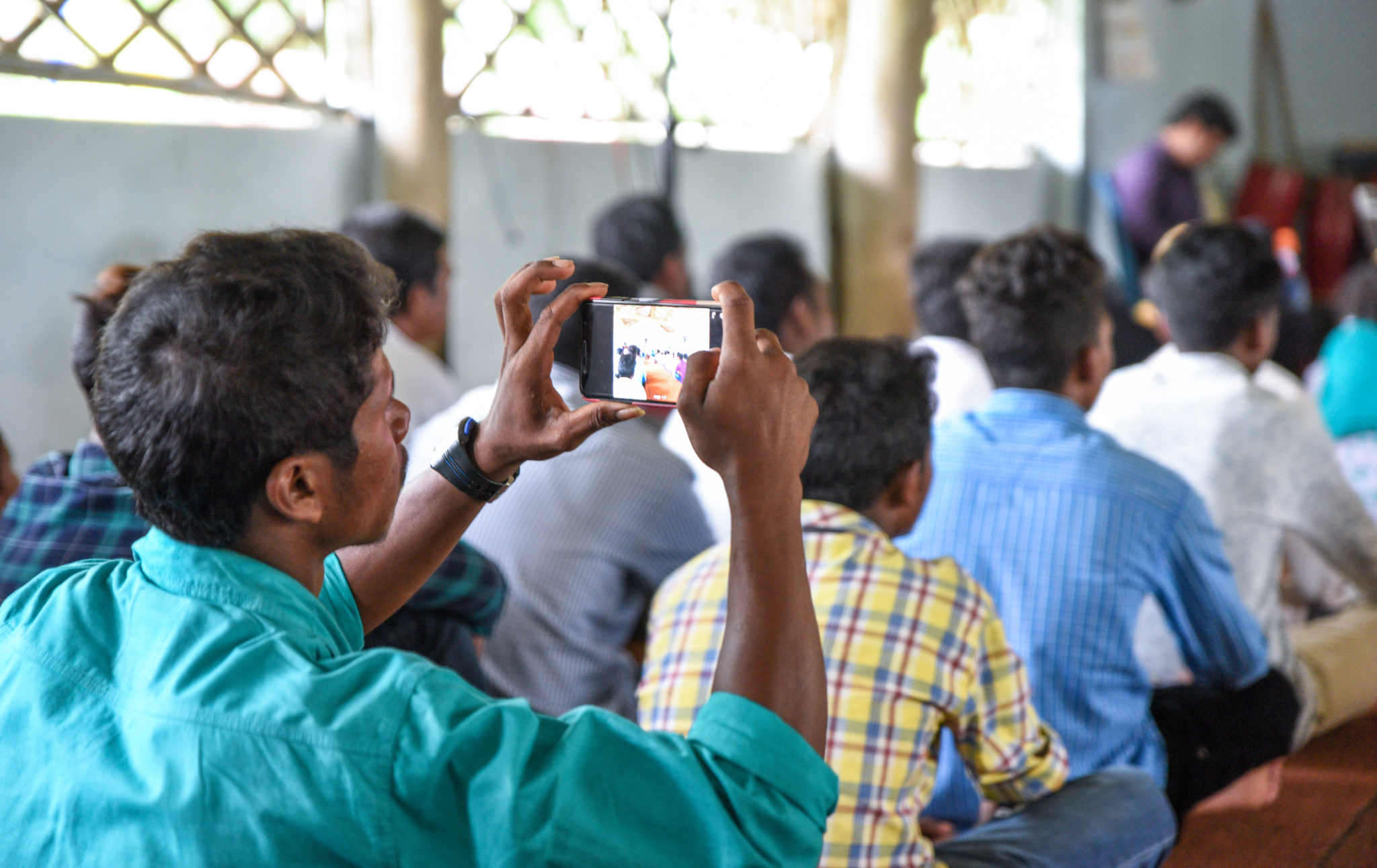 Indian man holds up smartphone to take photo during audio Bible app presentation