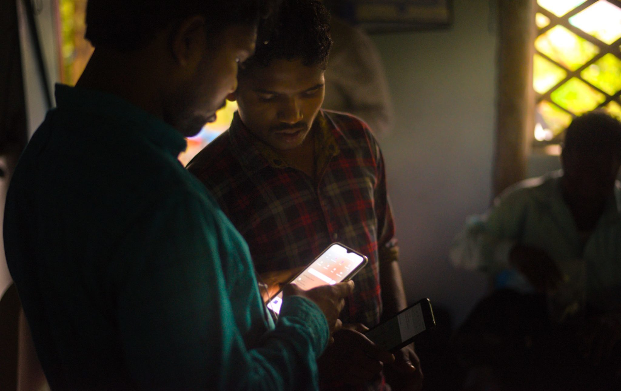 Two Indian men look at glowing smartphone screen with Hum auido Bible app