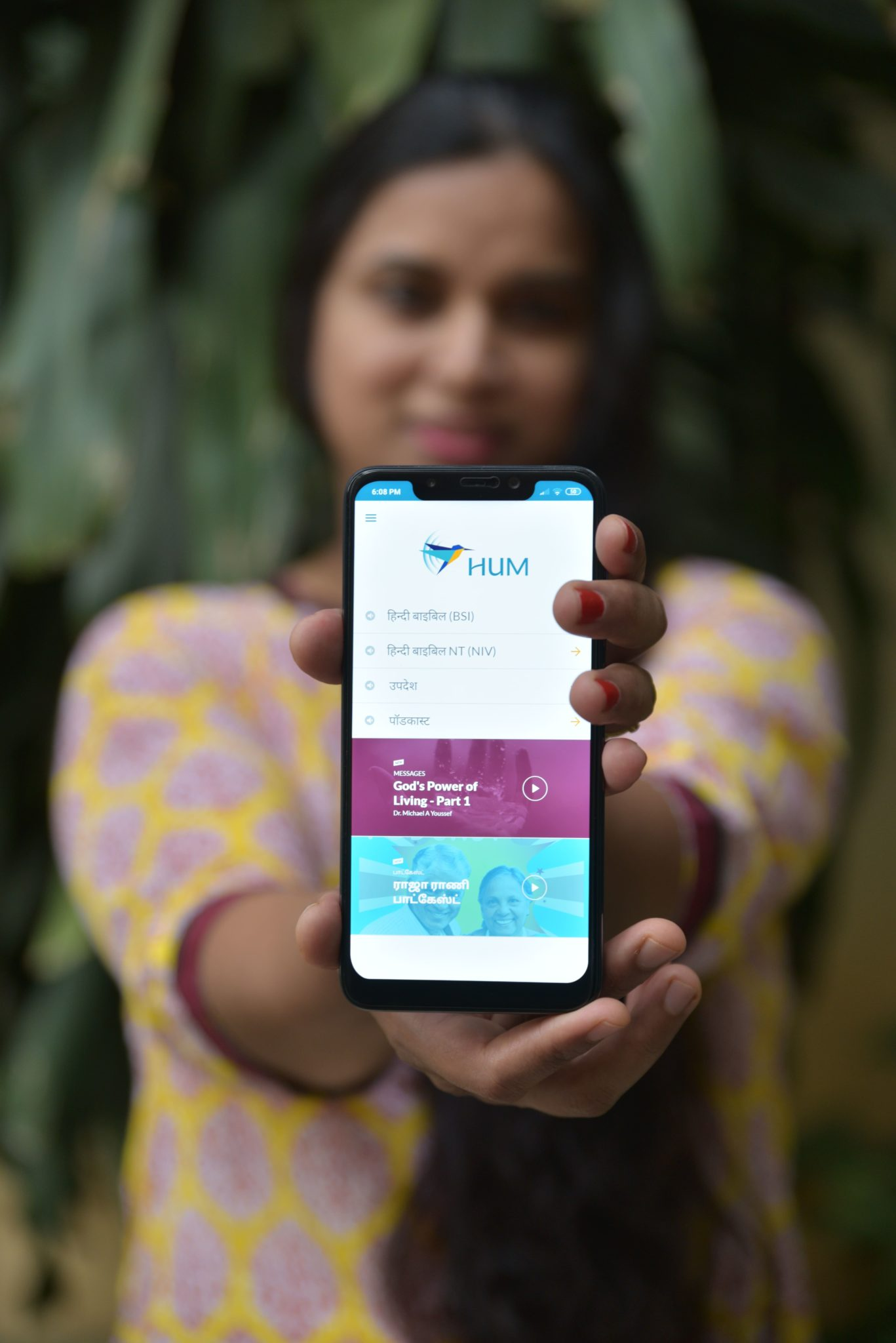 Indian woman holds out smartphone with Hum audio Bible app displayed