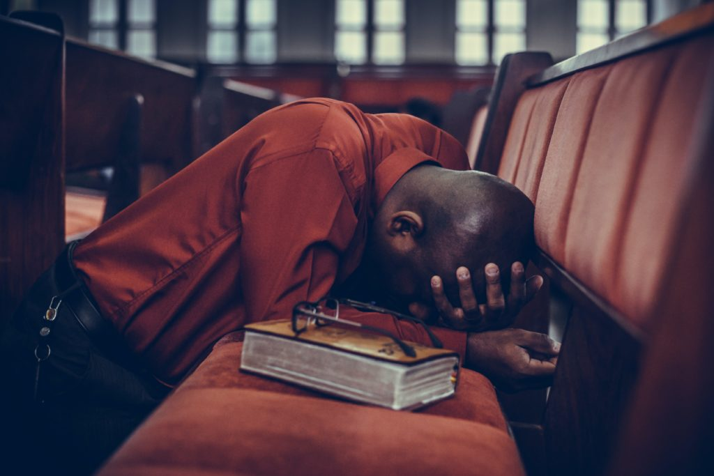 A man with his head in his hands kneels on a church pew next to a Bible.