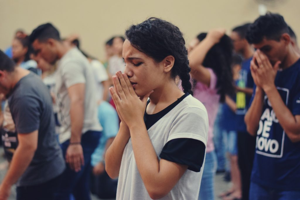 woman prays during group event