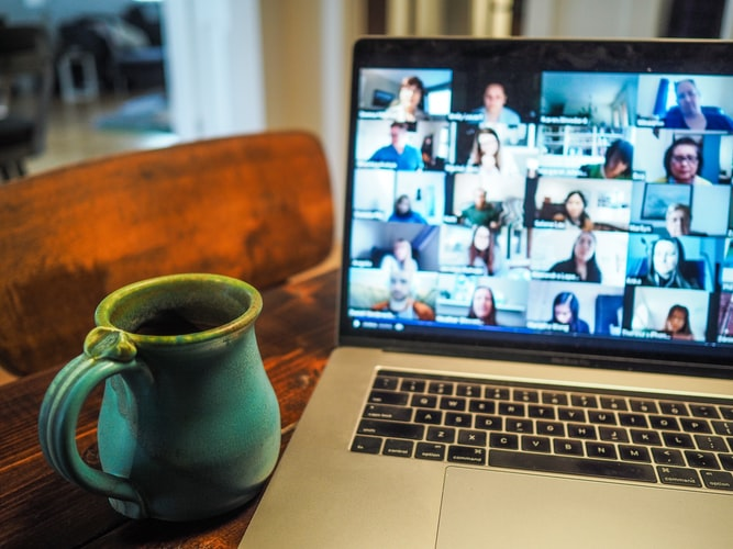 A laptop, next to a ceramic coffee mug, displays people on a video call.