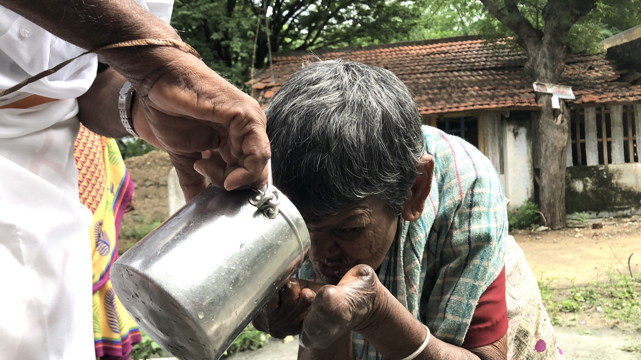 An elderly woman with leprosy drinks water from a silver bucket.