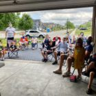 People sit in lawn chairs on a driveway while watching a church service together in a house church model.