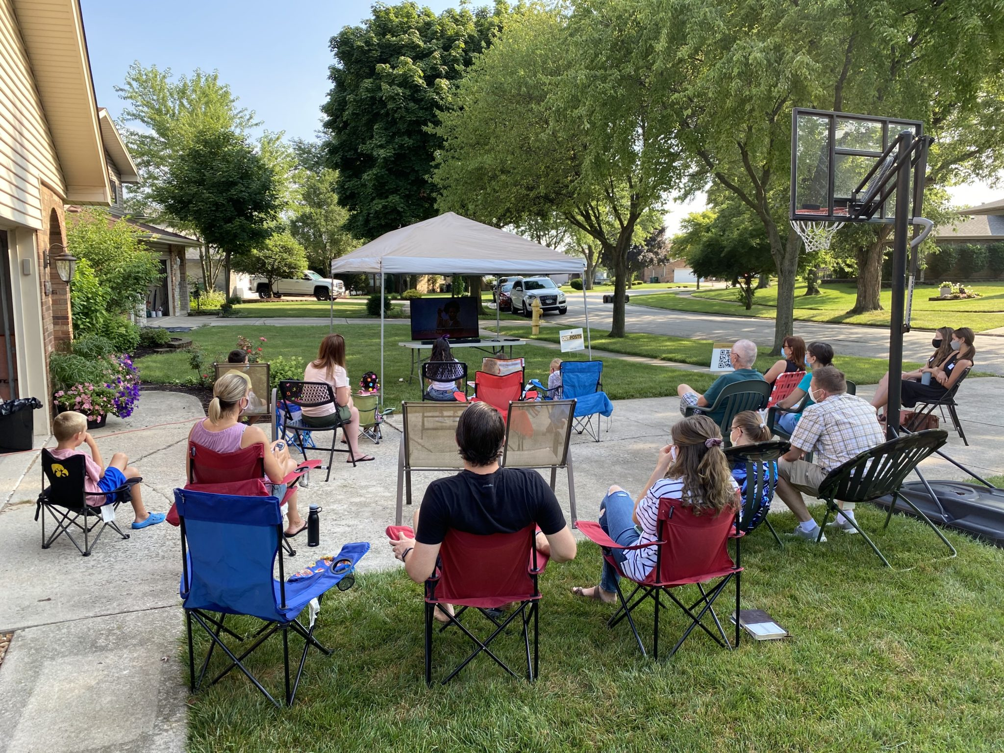 People sit in lawn chairs on a driveway while watching and discussing a church service together.