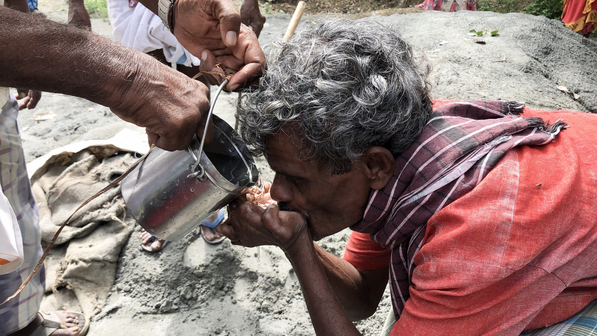 A gray-haired Indian man receives fresh water from a bucket into his cupped hands.