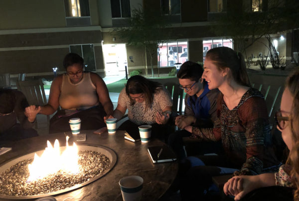A diverse group of young adults hold hands and pray around a campfire.