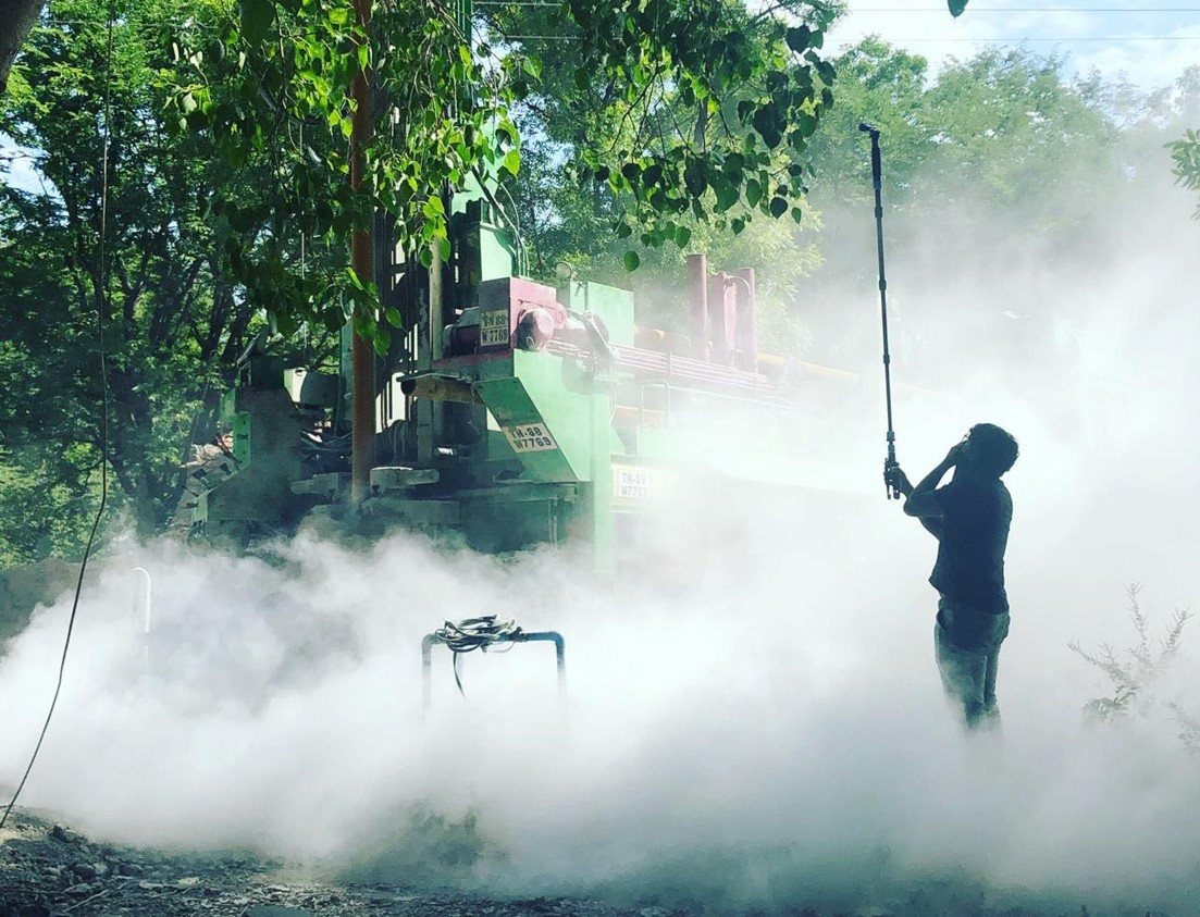 A man stands in a puff of dust while watching well-digging equipment.