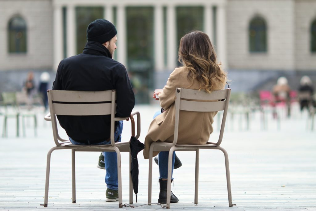 man and woman sitting on chair during daytime