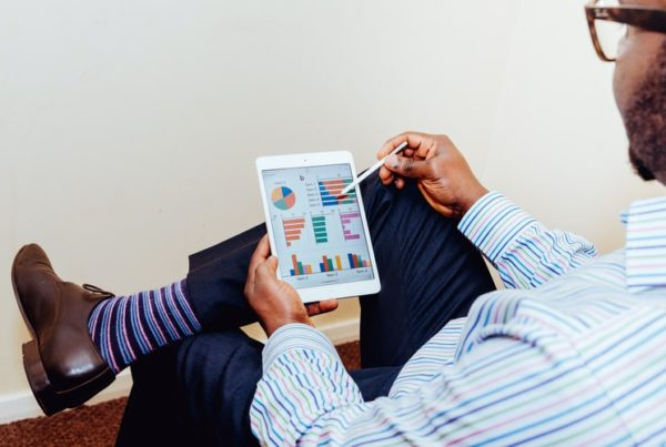 A man in business attire looks at his tablet screen of graphs and charts.