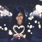 A young Asian woman holds a glowing heart-shaped string of lights with glimmers that extend across the dark background.