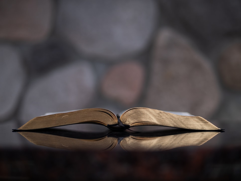 A Bible with gold-edged pages lies open on a table with a stone wall in the background.