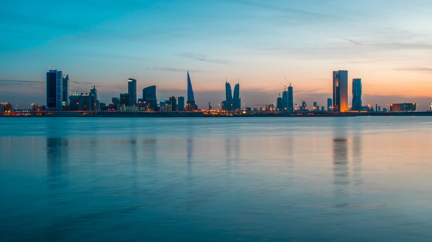 A city skyline in Manama, Bahrain, with water in the foreground and fading light.