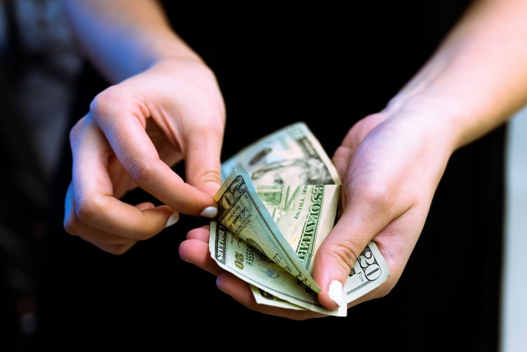 A close-up image of a young person's hands giving away $20 bills.