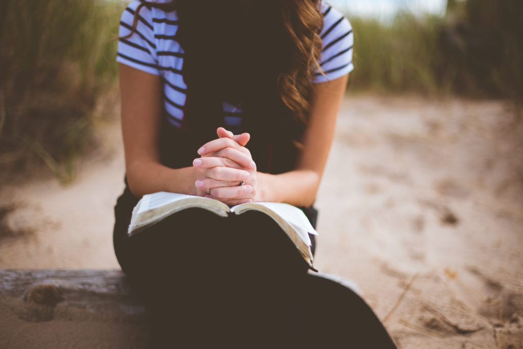 woman sitting on brown bench while reading book