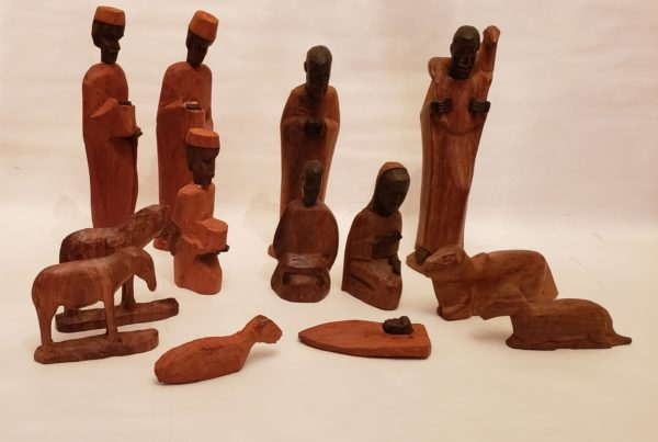 A wooden, African-style nativity against a white background