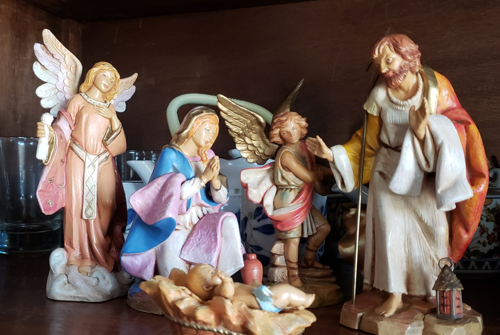A porcelain nativity shows Joseph, Mary, baby Jesus, and angels.