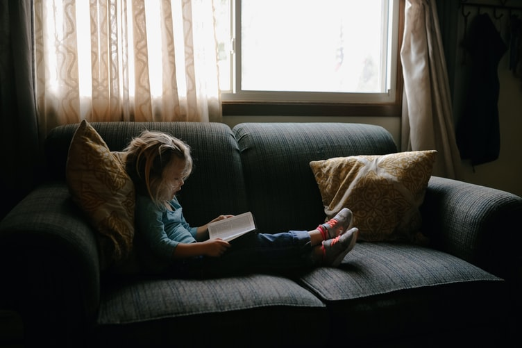 A young girl reads a book while sitting on a gray couch.
