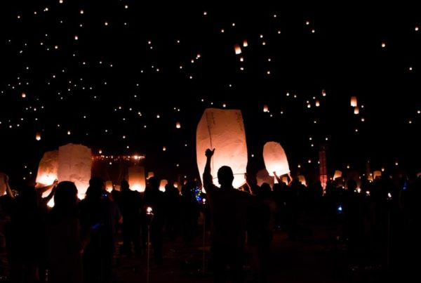 People lift glowing paper lanterns into the night sky.