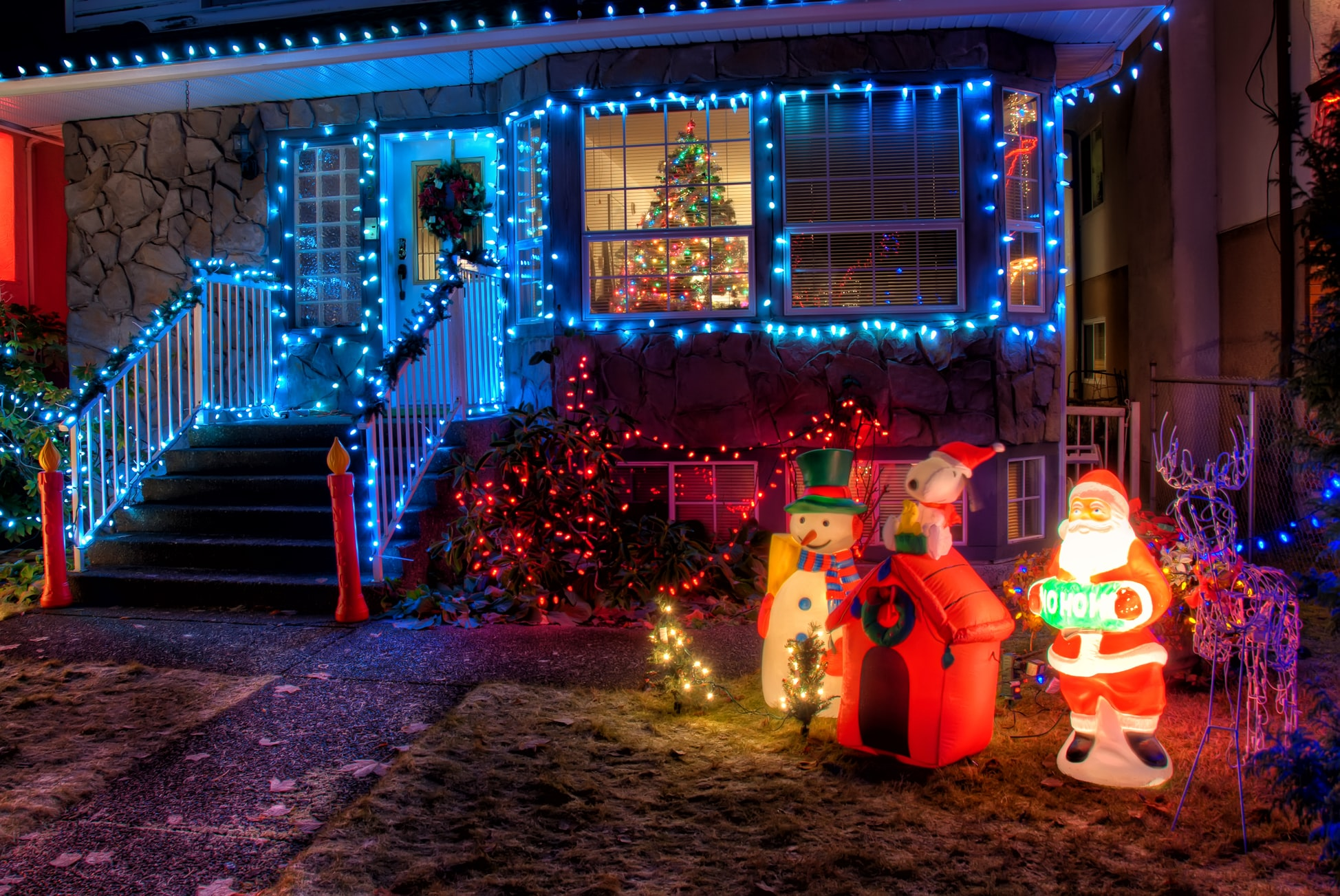 A yard displays Santa, Snoopy, and snowmen decorations in front of a house with light-lined windows and a Christmas tree.
