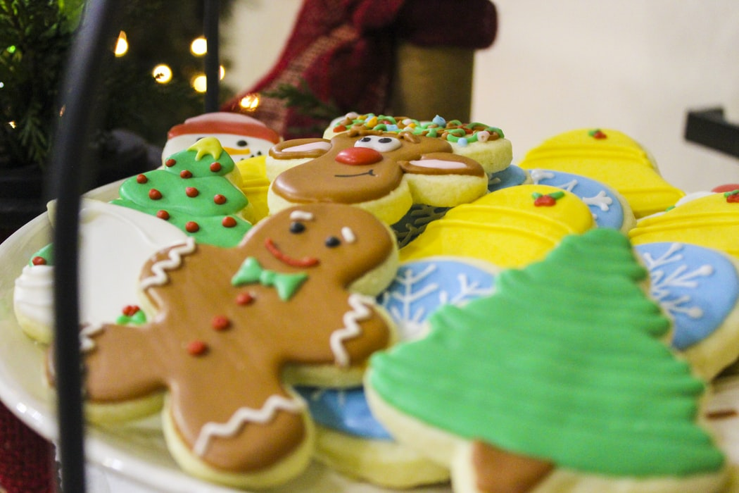 A plate of Christmas cookies include frosted Christmas trees and gingerbread people.