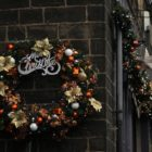 A Christmas wreath hangs on the side of a brick building.