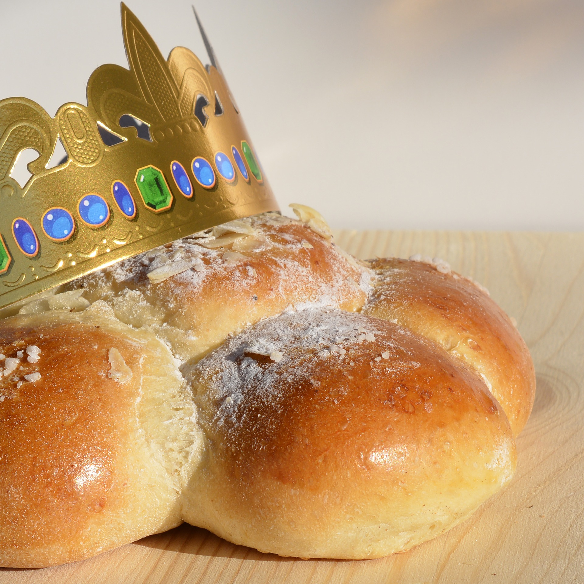 Glazed pastry buns compose a cake, dusted with powdered sugar, and topped with a golden paper crown.