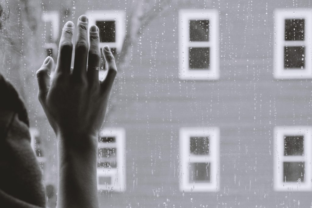 Person looking out window with hand raised