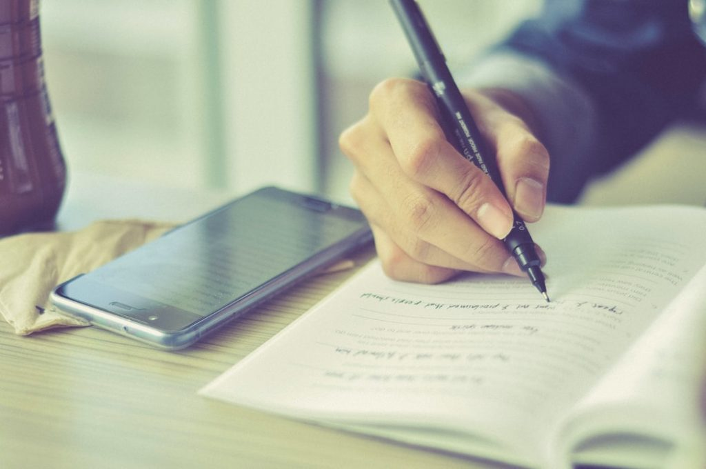 Close up image of a person writing in their notebook, with a phone beside.