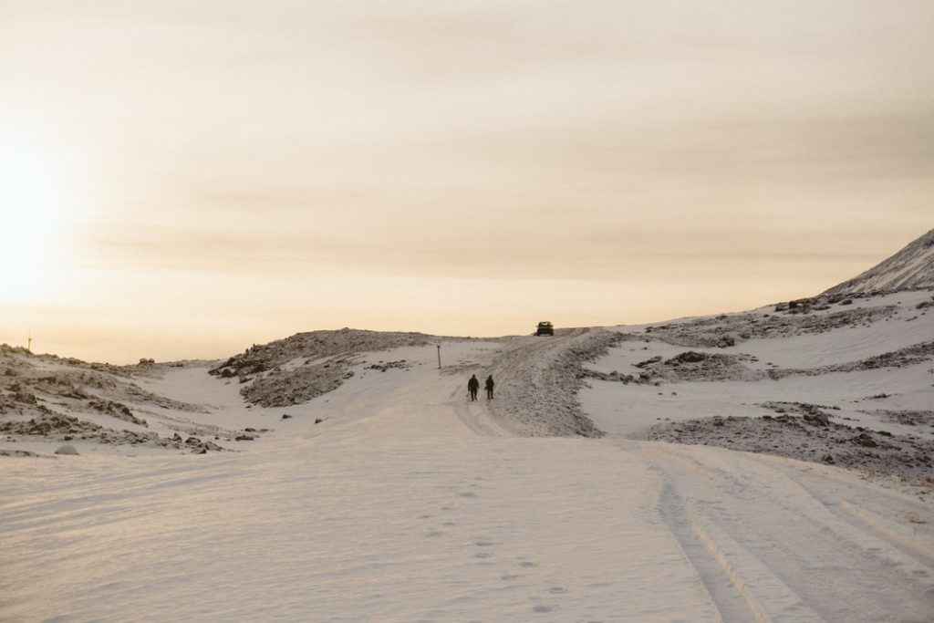 Two people walk up a snowy hill together, with footprints and tire tracks in the foreground.