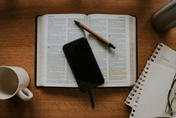 A phone and pen lie on top of an open Bible with highlighting. A journal and empty mug are beside.