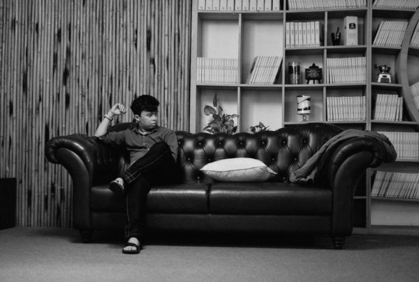 Black and white image of a young man sitting on one end of the couch in silence and solitude.