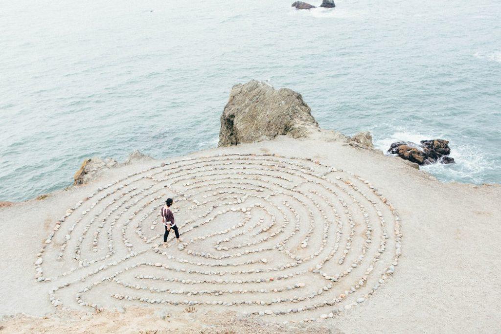 A woman walks through a labyrinth maze along the coast.