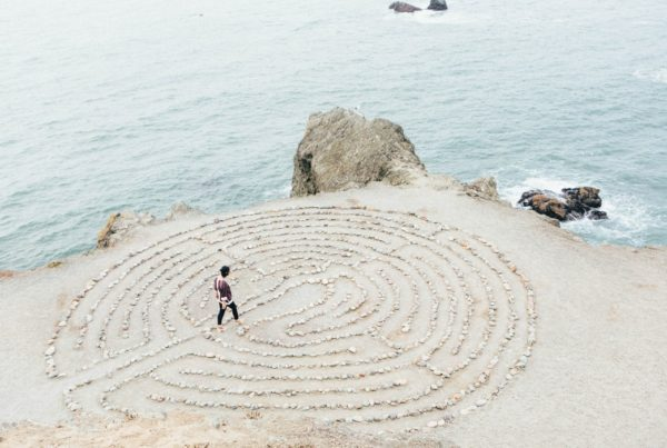 A woman walks through a labyrinth maze along the coast.