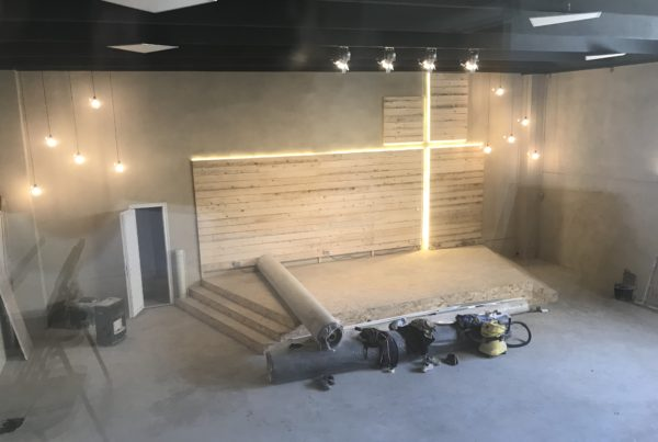 A church's interior is being constructed and a lit-up cross is at center stage.