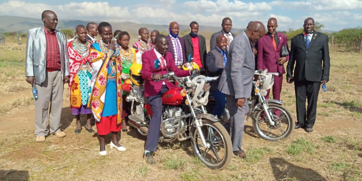 Maasai people in suits and colorful garb dedicate two motorbikes for evangelism efforts.