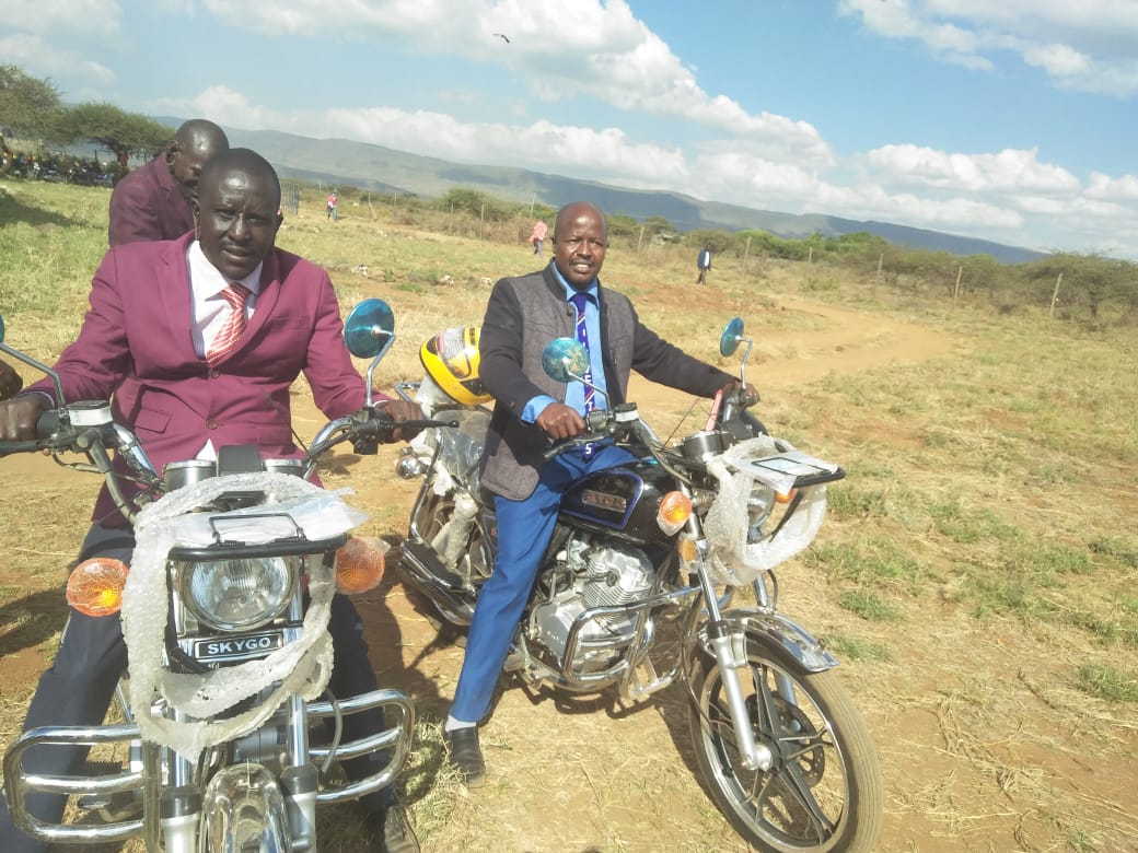 Two Kenyan pastors in suits smile as they try out their new motorbikes.