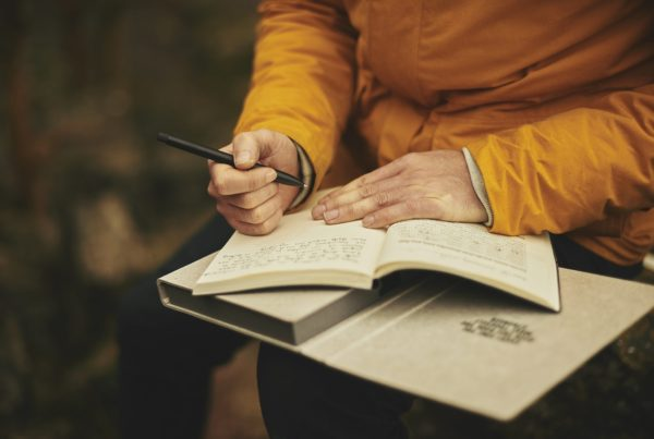Cropped image of adult in yellow coat writing in a journal.