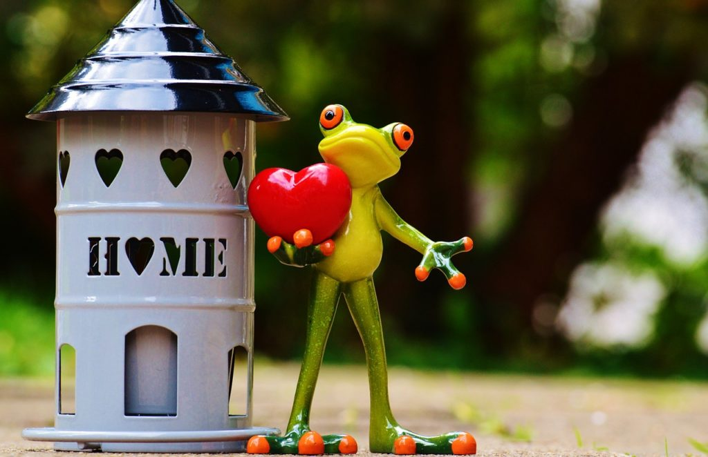 A frog statue holds a heart in front of a tin birdhouse that says home.
