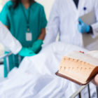 A hospital chaplain reads the Bible while doctors and nurses stand by.