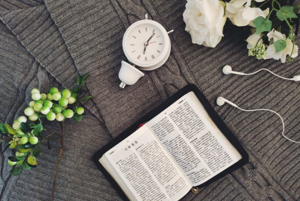 A clock and Chinese Bible lie on top of a gray knit blanket.