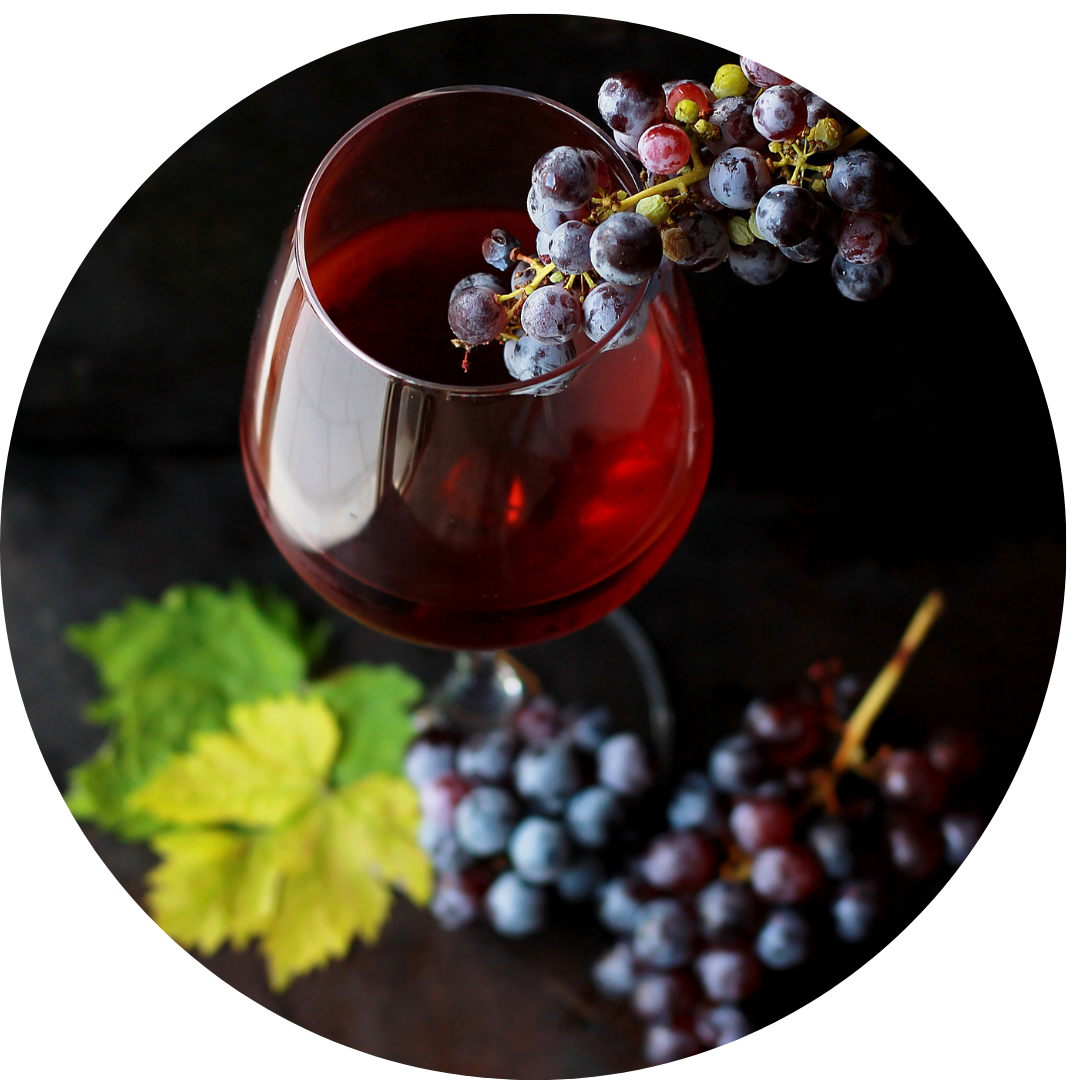 Red wine with grapes arranged around it