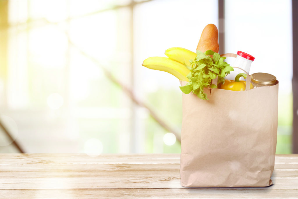 A brown paper bag of groceries contains bananas, greens, and a loaf of bread.