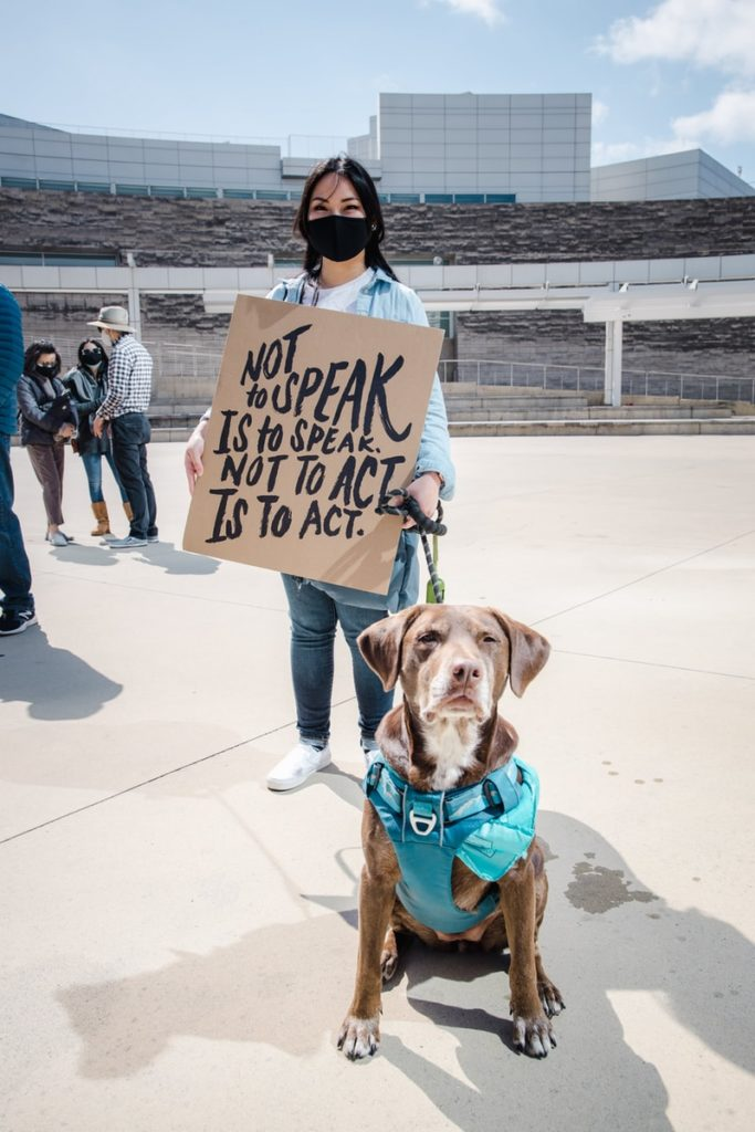 """A woman with a sign that says """"not to speak is to speak. Not to act is to act"""" with a guide dog."""