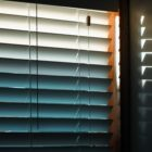 Sunlight through window blinds creates a blue and white gradation, with shadows on the wall.